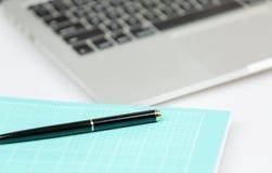 Laptop mit Stift- und Notizbuchvordergrund Stockbild