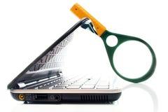 Laptop mit Vergrößerungsglas lizenzfreie stockfotos
