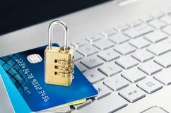 Laptop mit Vorhängeschloß und Kreditkarten auf Tastatur Stockfoto