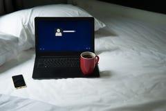 Laptop, mobiele telefoon en een kop van koffie op het bed Royalty-vrije Stock Afbeeldingen