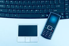 Laptop with Mobile Phone. Close up shot of mobile phone and a computer laptop Stock Photography