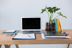 Laptop with mobile phone, clipboard, diary and pen on table Stock Photo