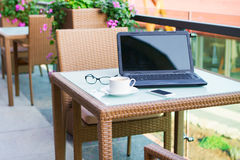 Laptop, mobile phone, glasses and coffee on a wood table in stre Royalty Free Stock Photo