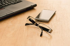 Laptop, mobile phone and glasses Royalty Free Stock Photos