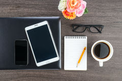 Laptop Mobile Phone and Tablet with notebook on the desk Royalty Free Stock Photos