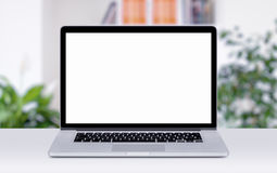 Macbook laptop mockup on table in office space. Front view of modern macbook laptop mockup with white blank screen on the office desk. Office space on the royalty free stock image