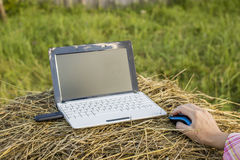 Laptop with modem lies on a haystack near a woman hold her hand Stock Photo