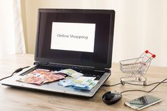Laptop with money. Mobile phone and shopping cart Stock Photography