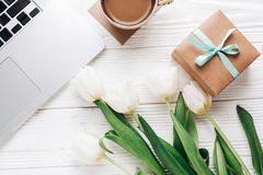 Laptop with morning coffee and tulips and stylish gift box on white wooden rustic background. flat lay freelance, work gadgets wi. Th space for text. spring stock image