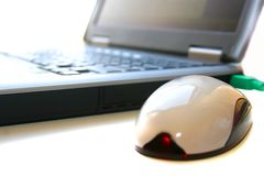 Laptop and a mouse. Black laptop and pluged infra red mouse Royalty Free Stock Photography