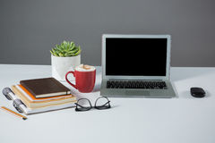 Laptop, mouse, cup of coffee with notebooks Royalty Free Stock Photo