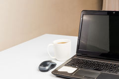 Laptop and mouse with a cup of coffee on office desk Royalty Free Stock Photos