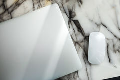 Laptop and mouse on table. Closed laptop and mouse on marble table from top view Stock Images