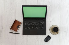 Laptop, mug of coffee and a notebook on the background of a wooden table. Top view Stock Photography