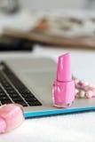 Laptop, mug and nail polish Stock Photos