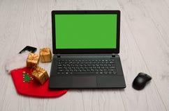 Laptop, muis, telefoon en Kerstmisdecoratie, Bureau Stock Foto
