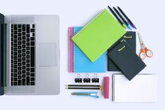 Laptop and Multiple Stationery Items. Multiple stationery items for office and school and a laptop from top view Royalty Free Stock Photos