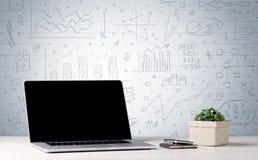 Laptop na biurku z biznesowymi mapami na ścianie Fotografia Royalty Free