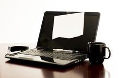 Laptop na biurku z pustym papierem nagrywającym pokazu ekran Zdjęcie Stock