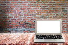 Laptop na drewnianych półkach z ściana z cegieł tłem Obrazy Stock