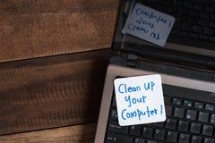 Laptop na drewnianym stole z notatką CZYŚCI UP TWÓJ komputer Obrazy Royalty Free