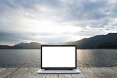 Laptop na drewnianym z ranku środowiskiem jezioro zdjęcie stock