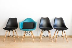 Laptop na krześle Błękitny krzesło wśród czerni na białym tle obrazy stock