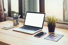 Laptop na stole w biurowym pokoju na nadokiennym miasta tle dla grafika pokazu montażu, obraz stock
