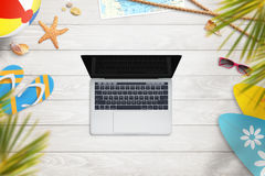 Laptop na white wooden desk surrounded by objects for summer vacation Royalty Free Stock Images