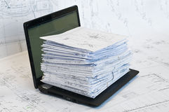 Laptop near pile of project drawings. Laptop and stack of project drawings on it. Working place royalty free stock photo