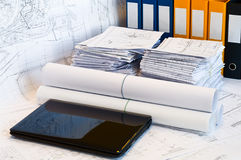 Laptop near pile of project drawings. Laptop and stack of project drawings. Rolled papers. Working place. White screen royalty free stock photo