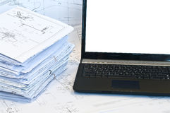Laptop near pile of project drawings. Laptop and stack of project drawings. Working place. White screen stock image