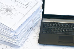 Laptop near pile of project drawings. Laptop and stack of project drawings. Working place. White screen royalty free stock image