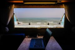 Work and leisure - succes. Laptop near window by the sea. Concept of working and leisure Stock Photography