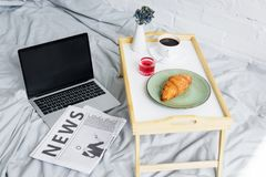 laptop, newspaper and breakfast with croissant and coffee on tray on bed stock photo