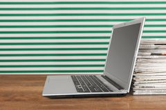 Laptop and Newspapers Stock Images