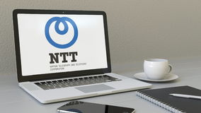 Laptop with Nippon Telegraph and Telephone Corporation NTT logo on the screen. Modern workplace conceptual editorial 3D Stock Images
