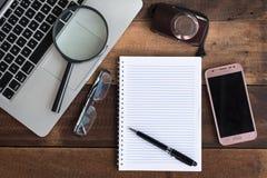 Laptop, notatnik, smartphone, widowisko, kamera i powiększać, - szkło na drewnianym stole zdjęcie stock