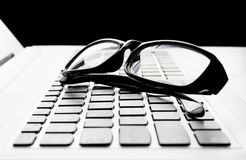 Laptop or Notebook Button and Black Glasses  on Black Background Stock Photography
