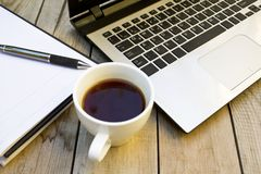 Laptop, notebook and coffee cup on wooden table. stock photo