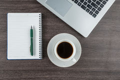 Laptop, notebook and coffee cup on work desk Royalty Free Stock Photos