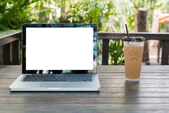 Laptop Notebook with iced coffee cup on wooden table Stock Images