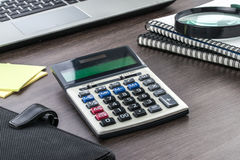 Laptop, notebook and Magnifier with Calculator on the desk Stock Images