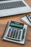 Laptop, notebook and pen with calculator on the desk Stock Photos