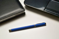 Laptop, notebook and pen. On the desktop Royalty Free Stock Photo