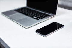 Laptop,notebook and phone, smartphone on the table.Office desk t royalty free stock image