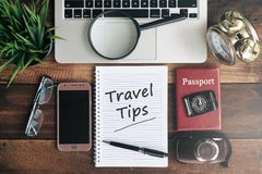 Laptop, notebook, smartphone, passport, compass, magnifying glass and clock with TRAVEL TIPS word. On wooden table. travel concept Royalty Free Stock Images
