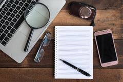Laptop, Notebook, smartphone, spectacle, camera and magnifying glass on wooden table Stock Photo