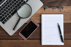 Laptop, Notebook, smartphone, spectacle and magnifying glass on wooden table Royalty Free Stock Photo