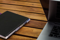 Laptop and notebook on table. Laptop and notebook on wood table in garden Royalty Free Stock Image